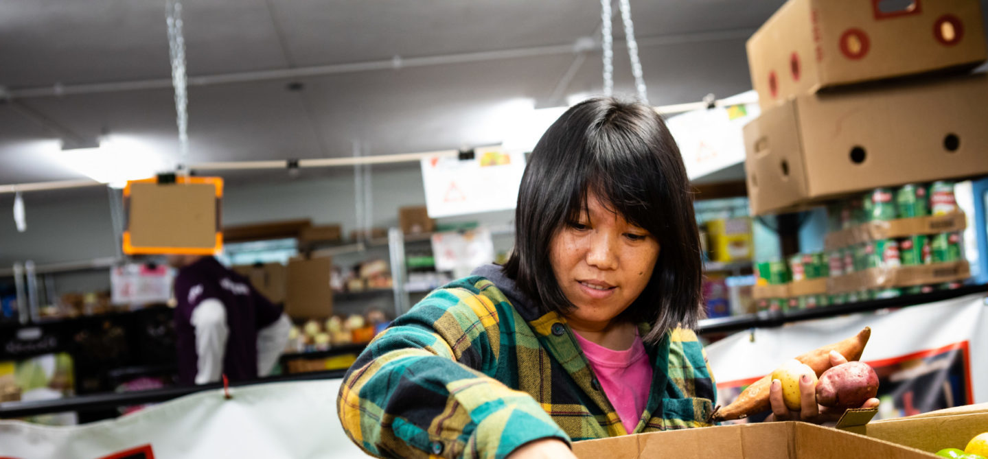 a woman selecting produce from a food pantry