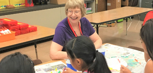 volunteer art teacher at table with students
